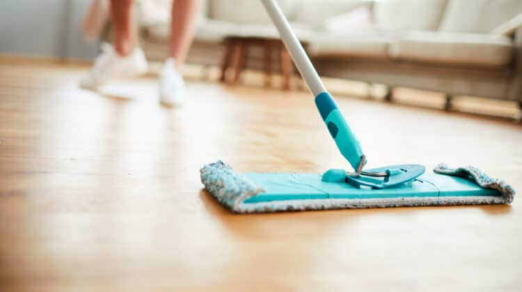 Woman using a microfiber mop on a wood floor