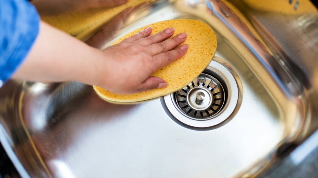 Woman polishing stainless steel sink with homemade cleaner