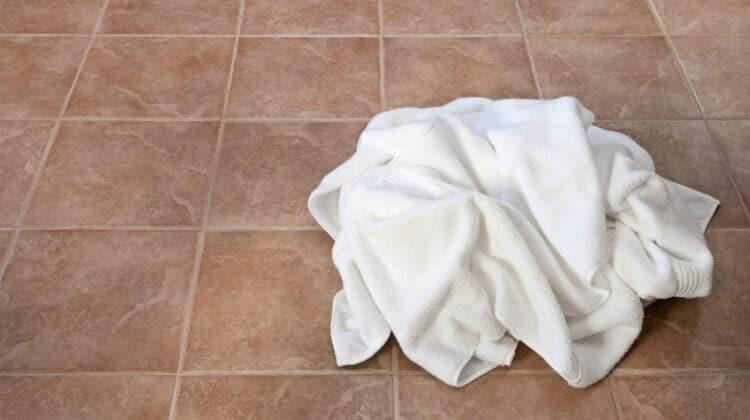 White towel in heap on tile bathroom floor