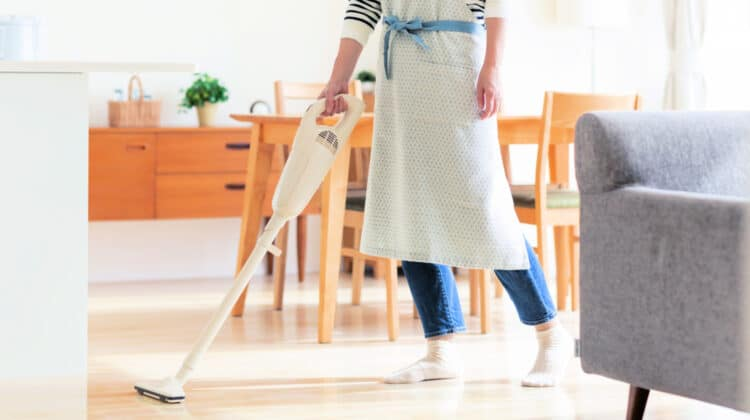 Person using a stick vacuum to clean high traffic area on a wood floor as part of the daily house cleaning routine