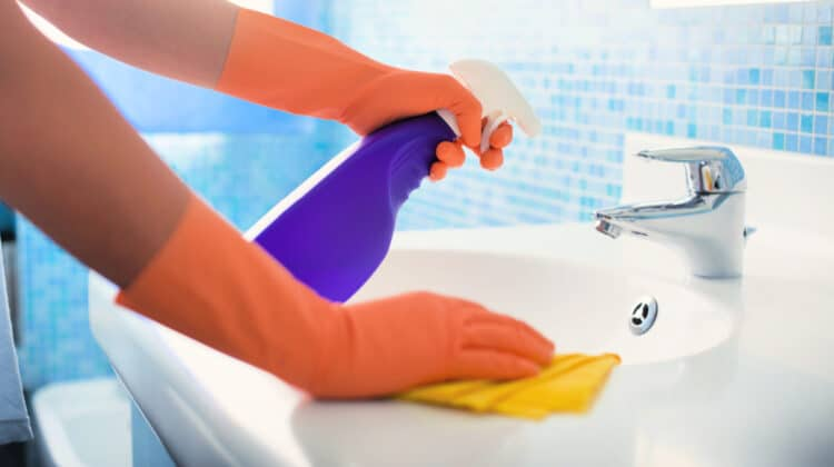 Woman wiping bathroom sink as part of her daily house cleaning routine