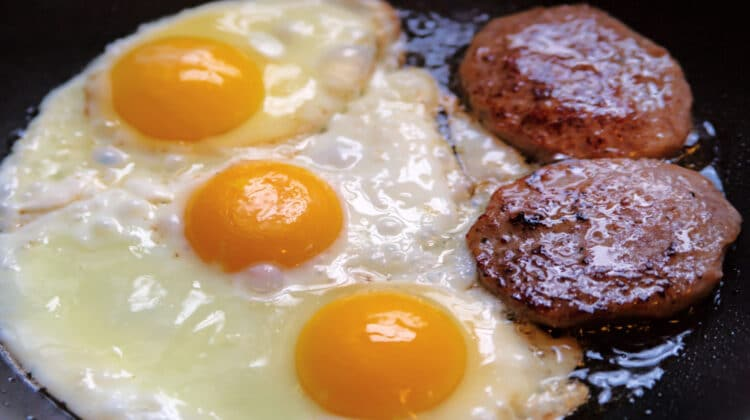 Closeup of three eggs and two homemade breakfast sausage patties frying in a cast iron skillet