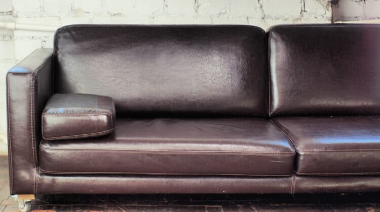 A well-conditioned brown artificial leather sofa on wheels sits in front of a bare brick wall