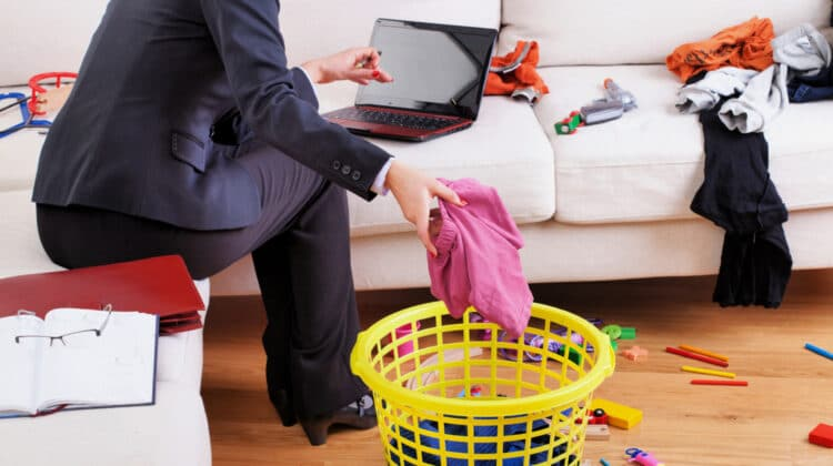 Working female in business suit sits on a sofa using a laptop as she folds laundry