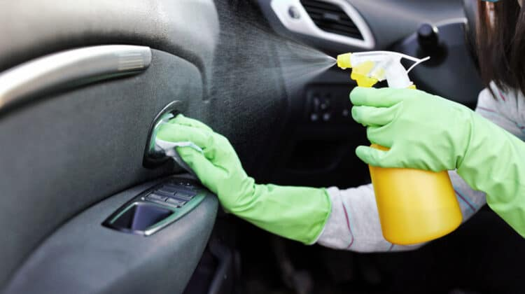 Closeup of woman wearing gloves and using homemade spray to clean her car's interior