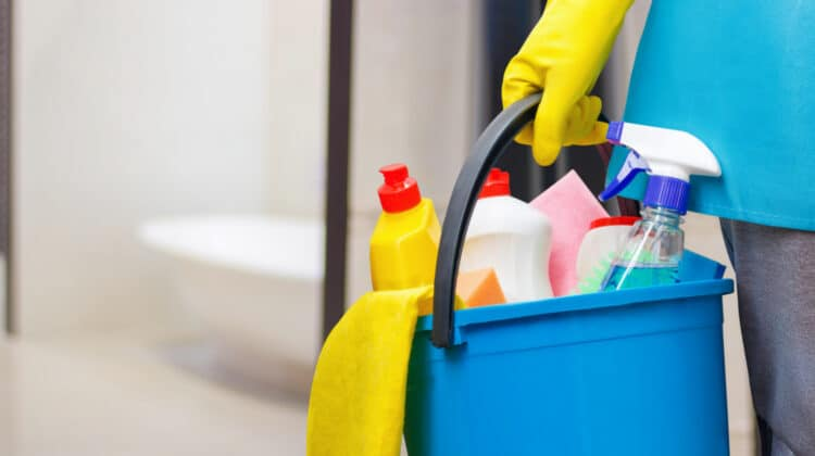 Concept shot of a person dressed as a professional house cleaner carrying a bucket of cleaning supplies with a bathtub in the backgorund