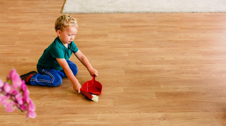 Little boy using hand broom and dust pan to sweep floor