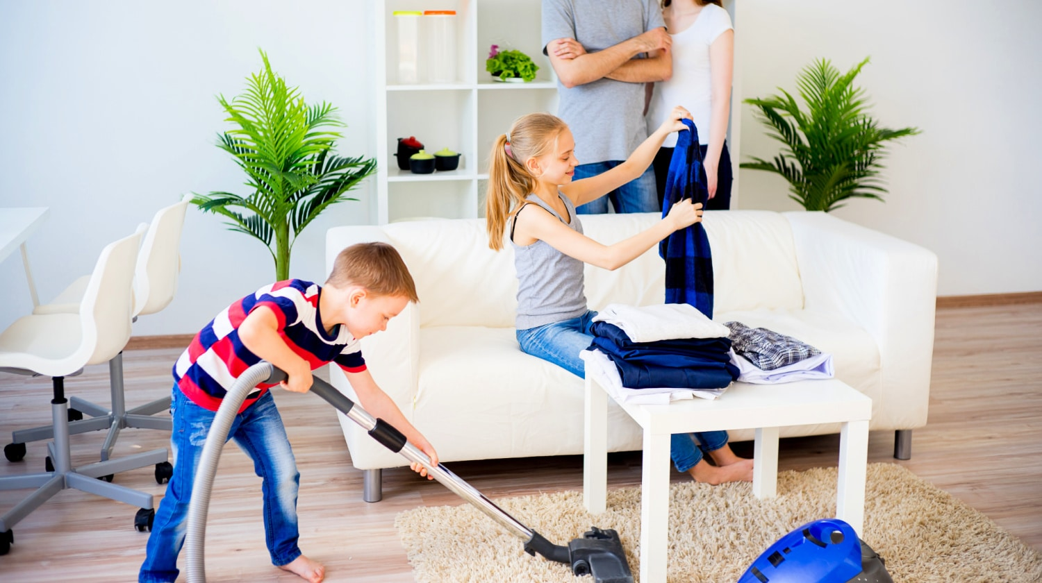 School-age children doing age-appropriate chores around the house while parents watch