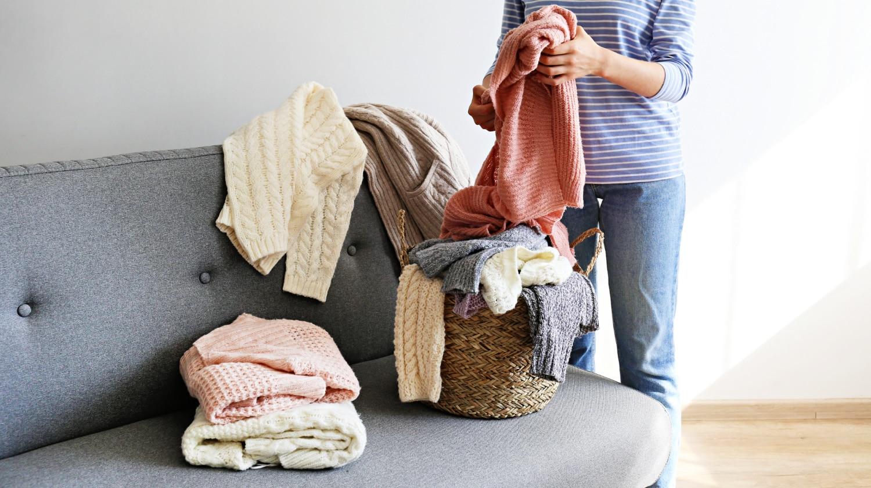 Woman folding sweaters on sofa