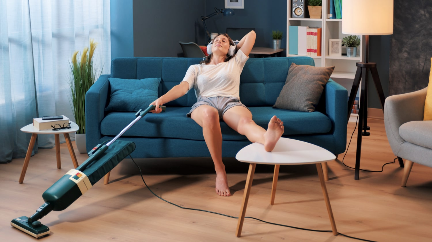 Woman in the middle of cleaning sits on sofa listening to music