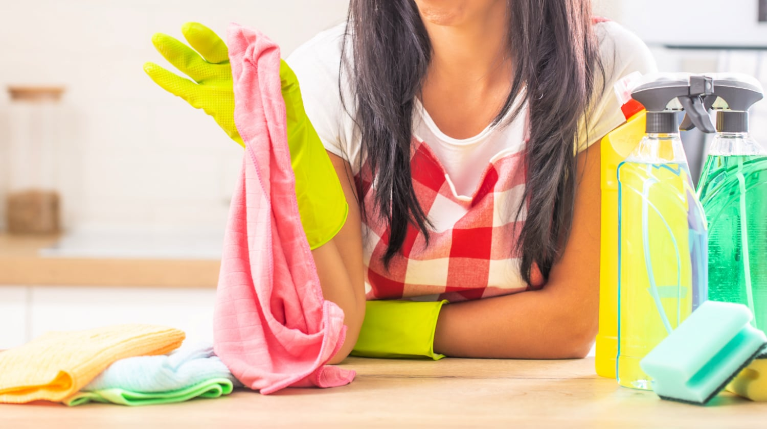 Woman leaning on counter and holding up a microfiber cloth