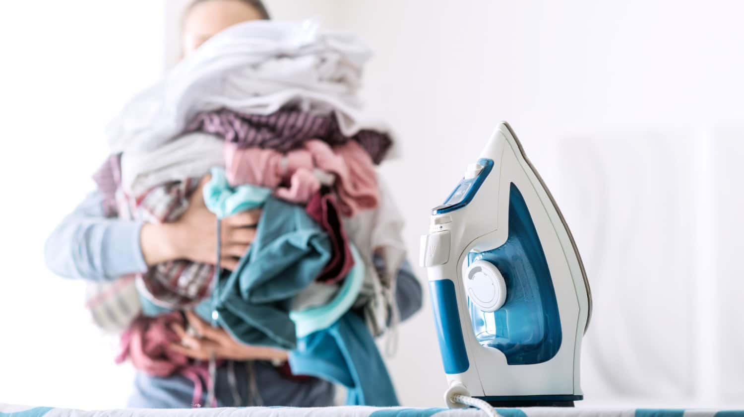 Teenager carrying pile of clothes to ironing board to demonstrate chores that teens can do