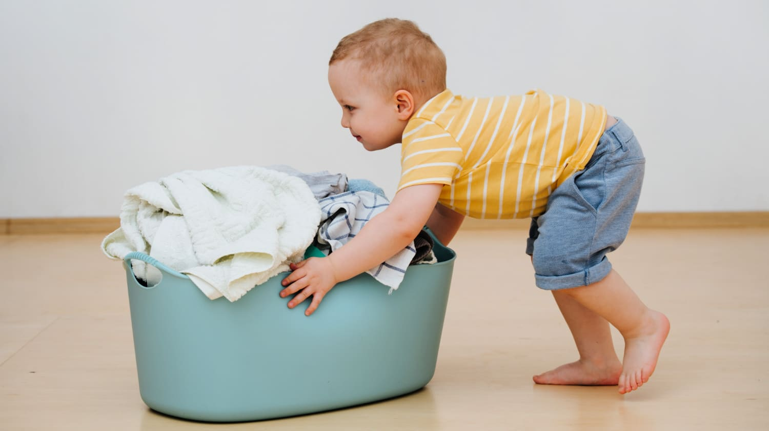 Toddler boy pushes a hamper of laundry across the floor to show age-based chores that kids can do