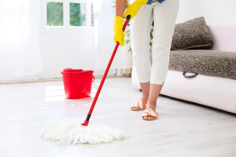 Woman using homemade floor cleaner in bucket to mop laminate flooring