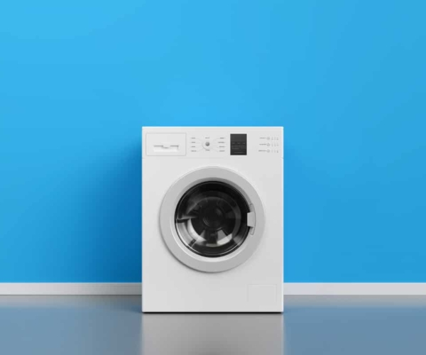 Front load washing machine sitting in front of a blue wall