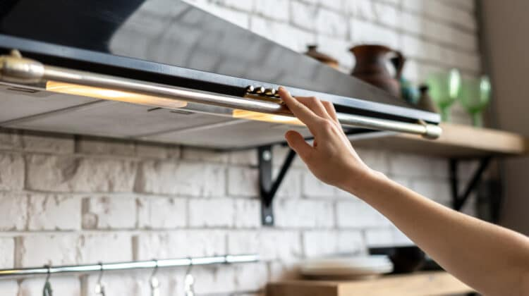 Woman adjust light on stove hood with dirt filters