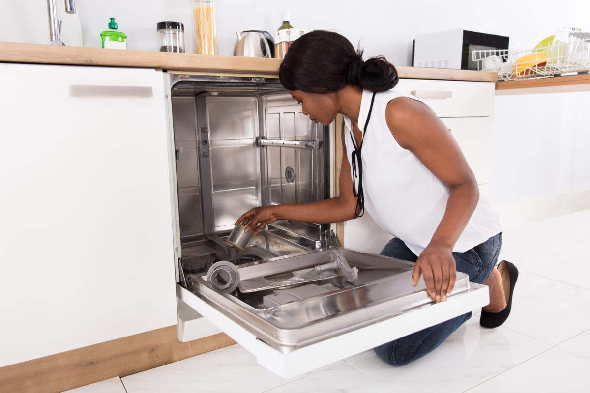 Woman kneeling next to open dishwasher and removing the filter to clean it