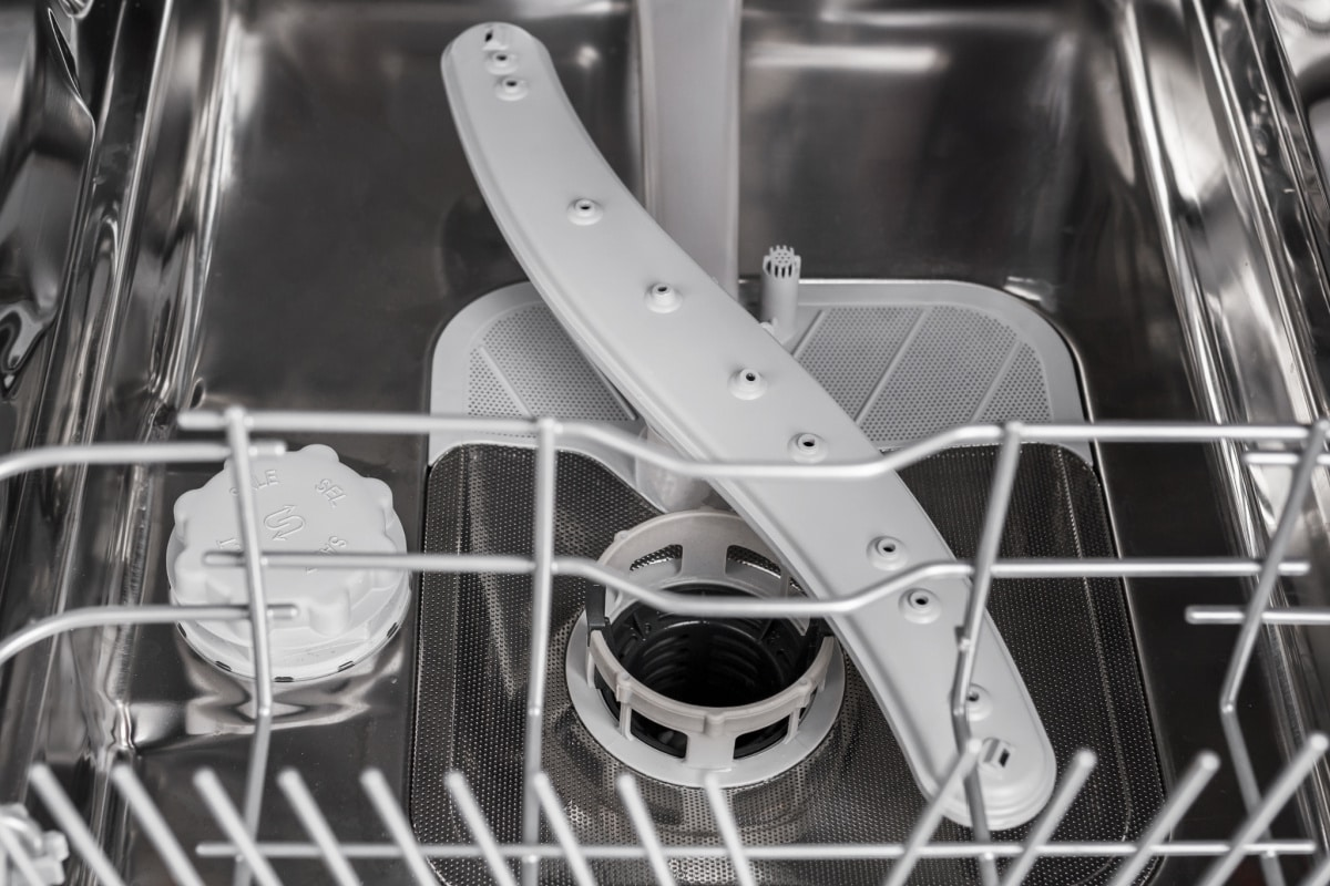 Interior view of racks, spinning arm, and filter in a clean dishwasher