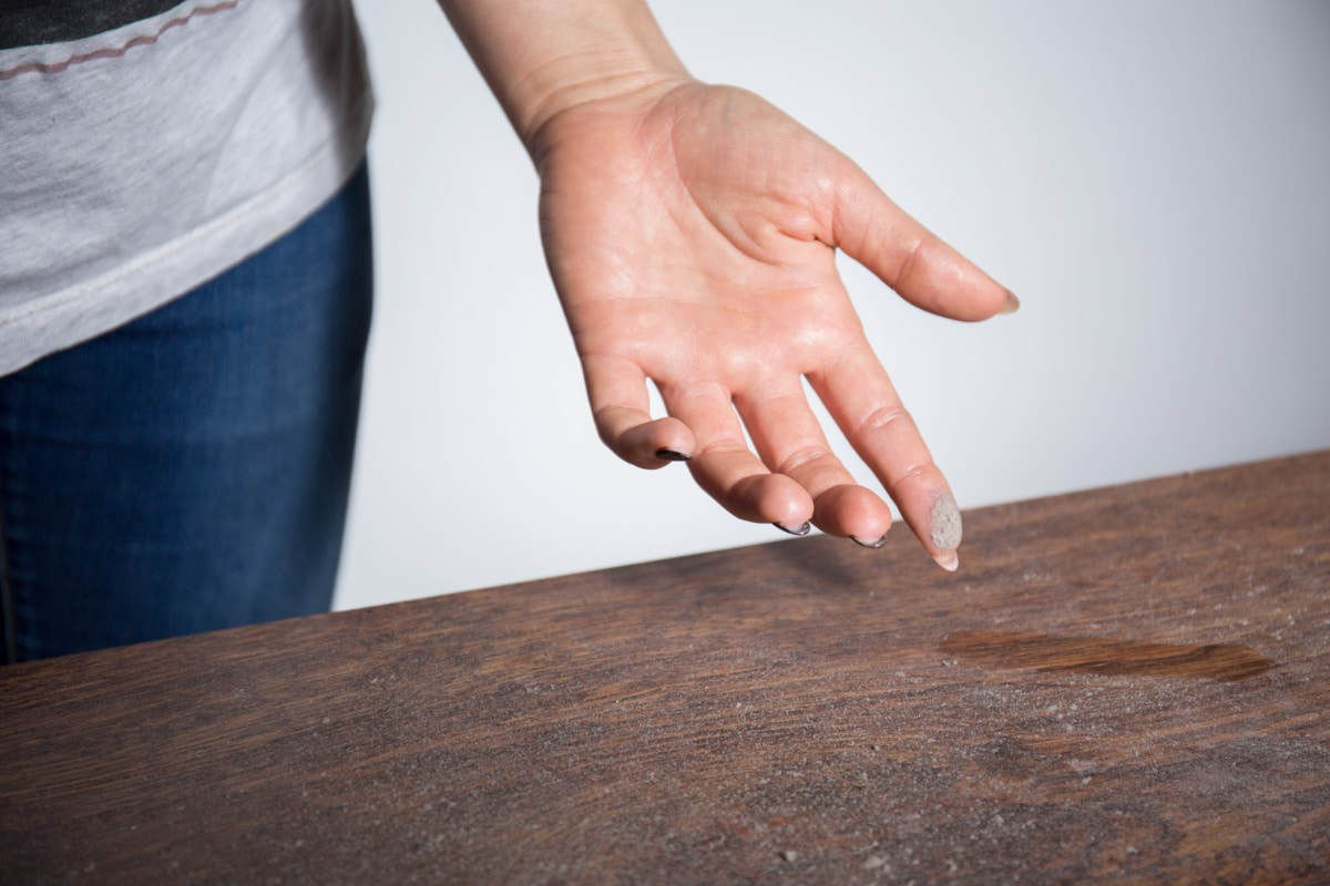 Female stands next to dusty table and shows dust collected on her fingertip