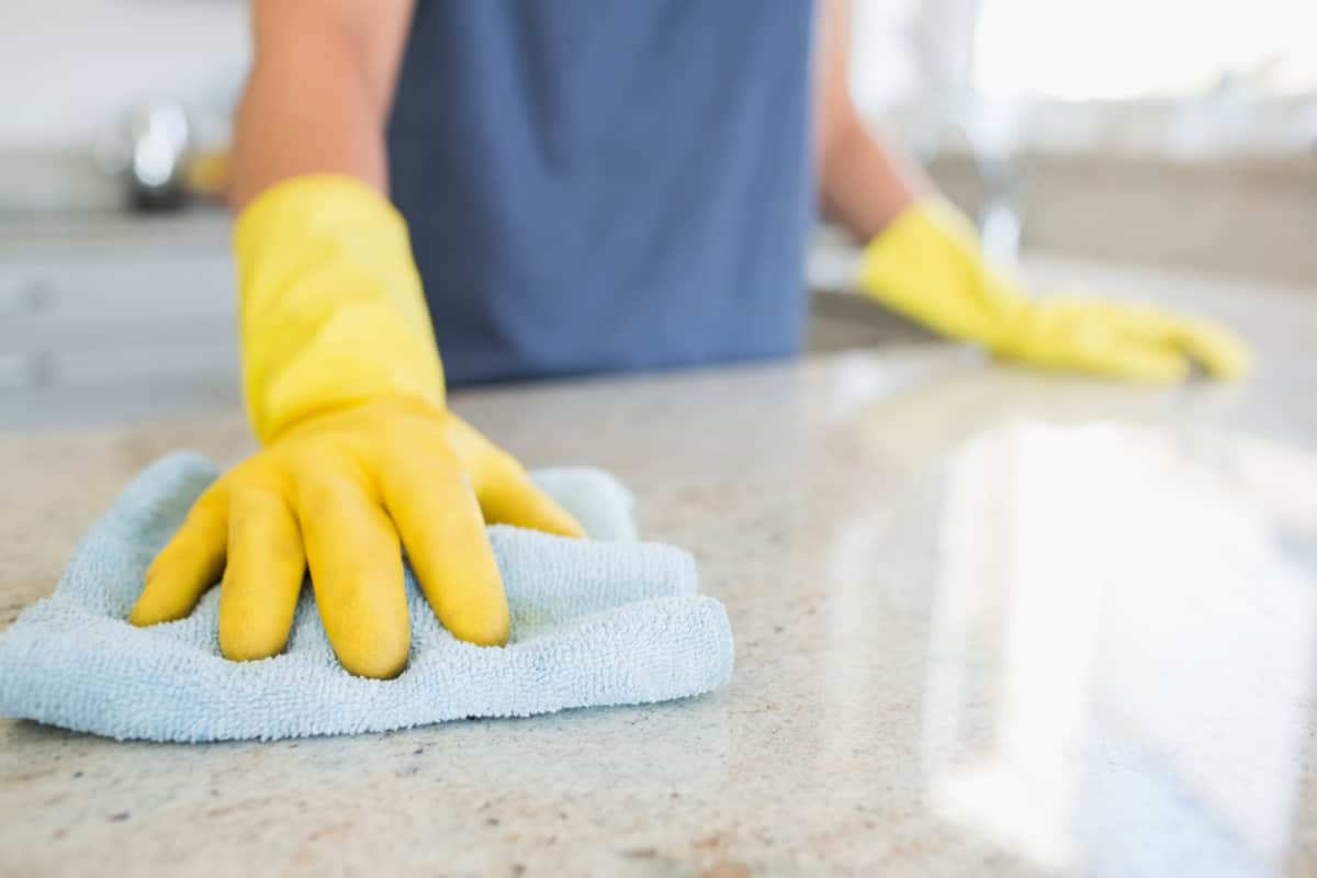 Person wearing rubber gloves using microfiber cloth to clean granite kitchen counter for Spring Cleaning