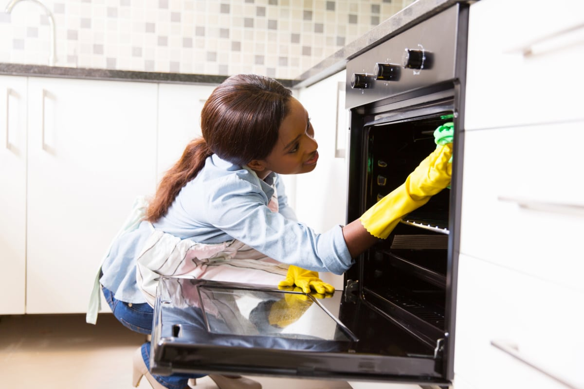 Woman spring cleaning oven in modern kitchen