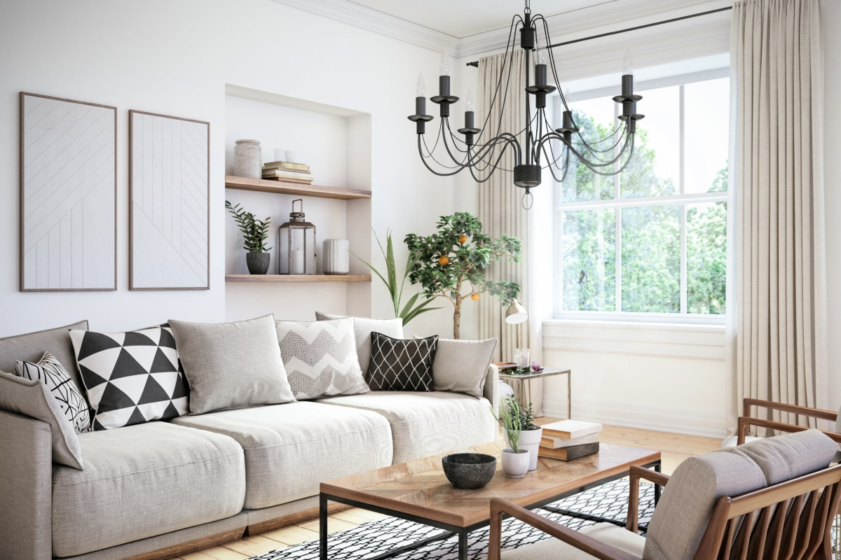 Modern living room with neutral furniture, a metal chandelier, and an orange tree