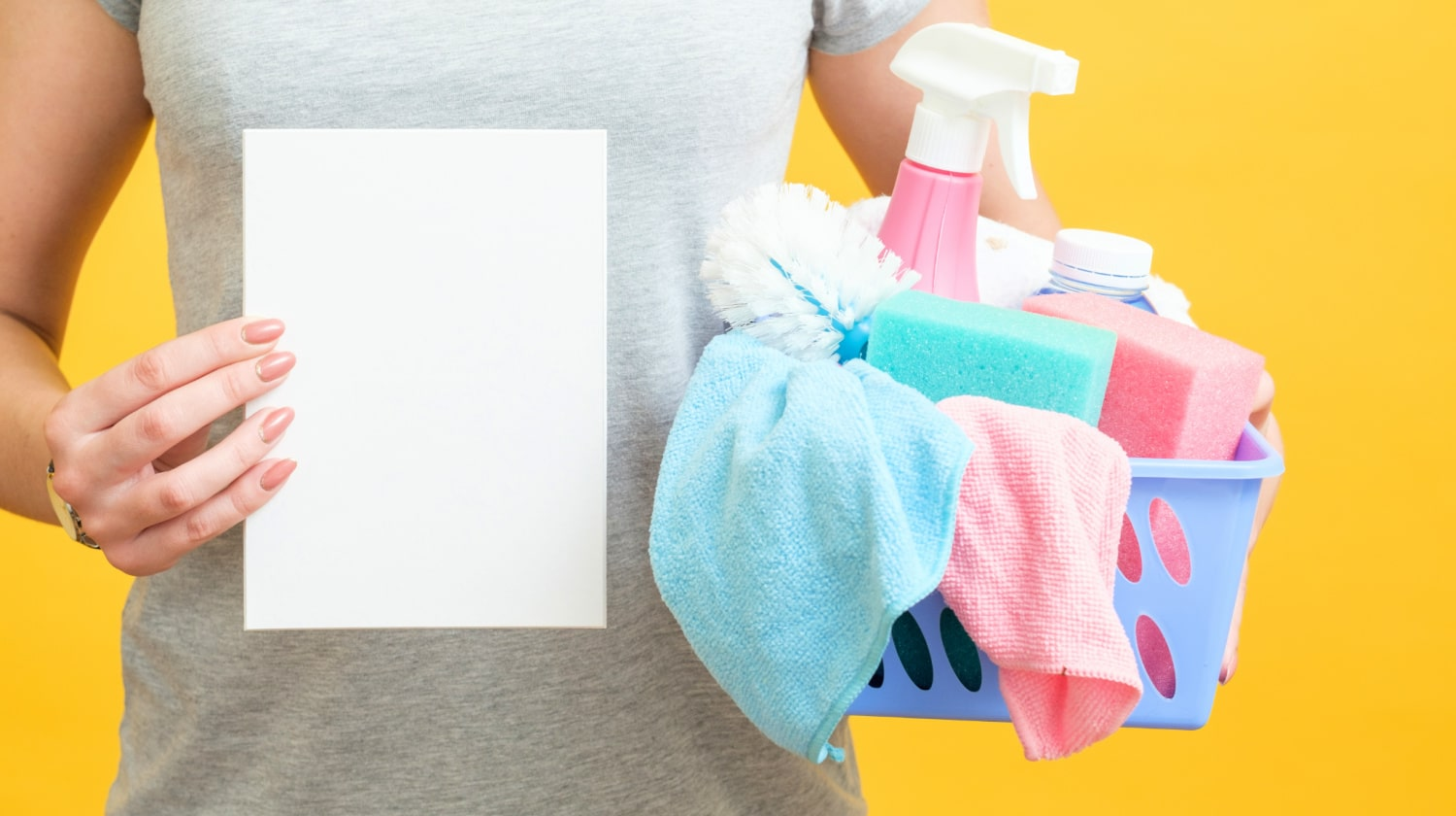 Female holds a basket of cleaning supplies in one hand and a blank sheet of paper in another