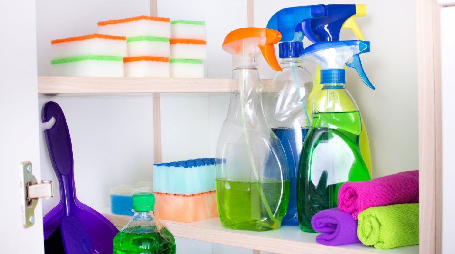 Cleaning tools and supplies in an open cupboard