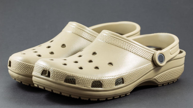 A pair of beige crocs on a dark background