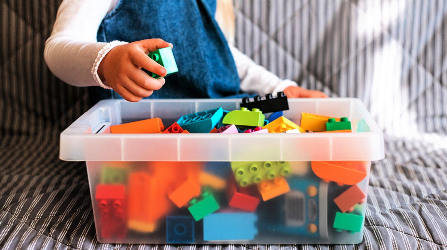 Child sits behind clear box of large Legos on sofa