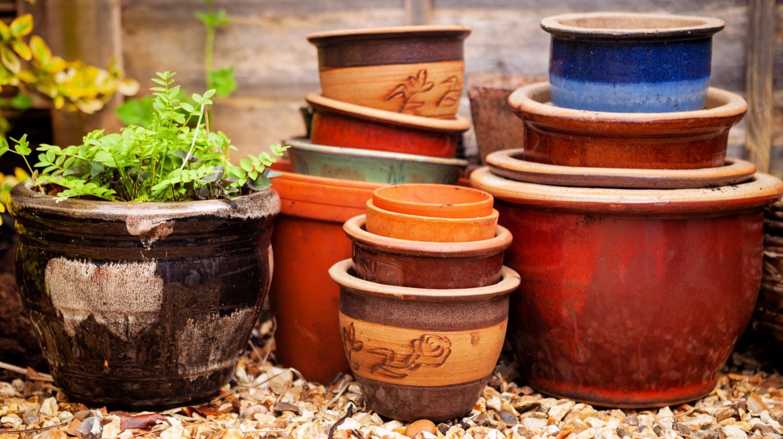 Empty garden flower pots on a bed of rubble
