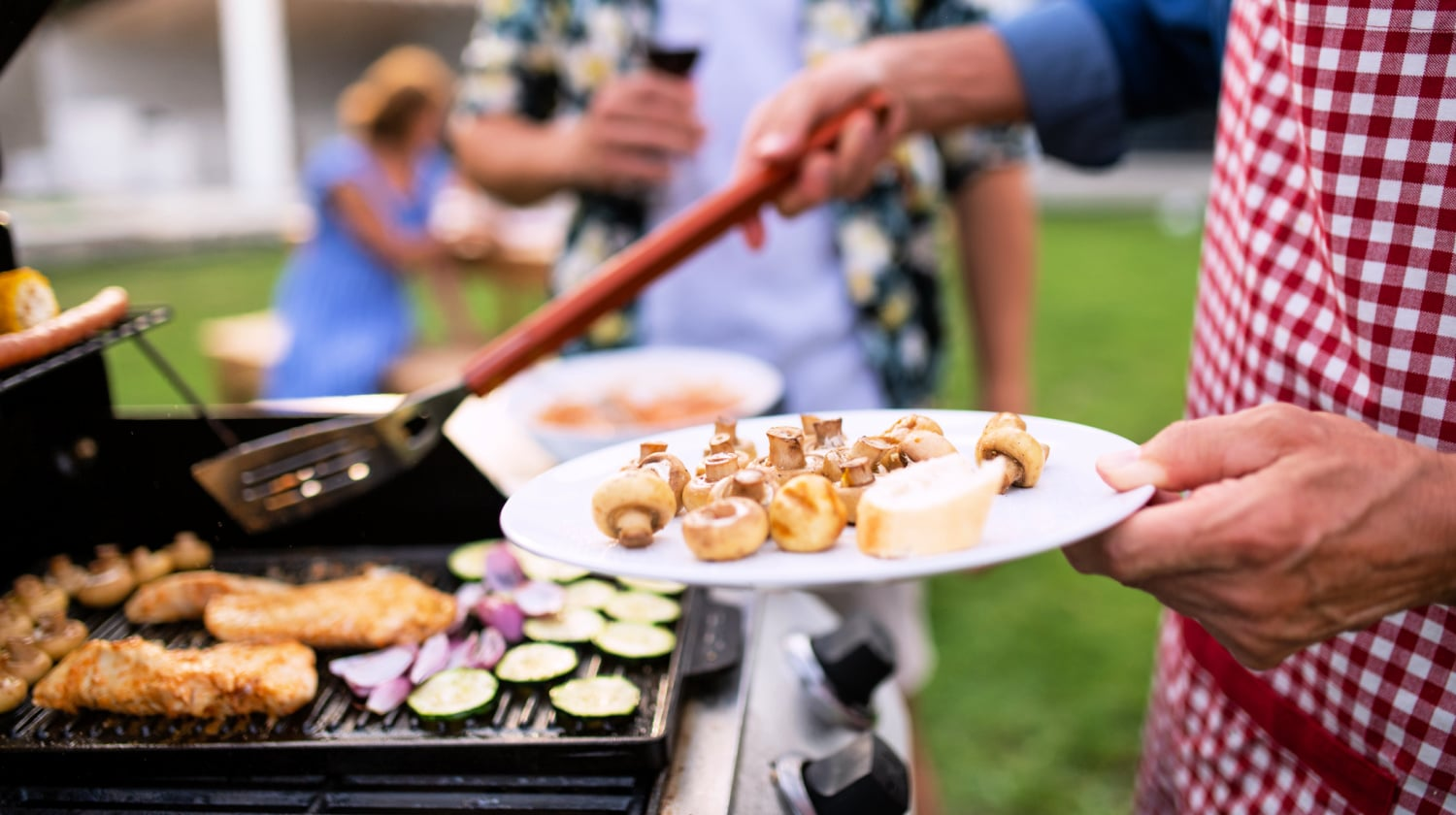 Side view of male standing at outdoor grill cooking meats and vegetables