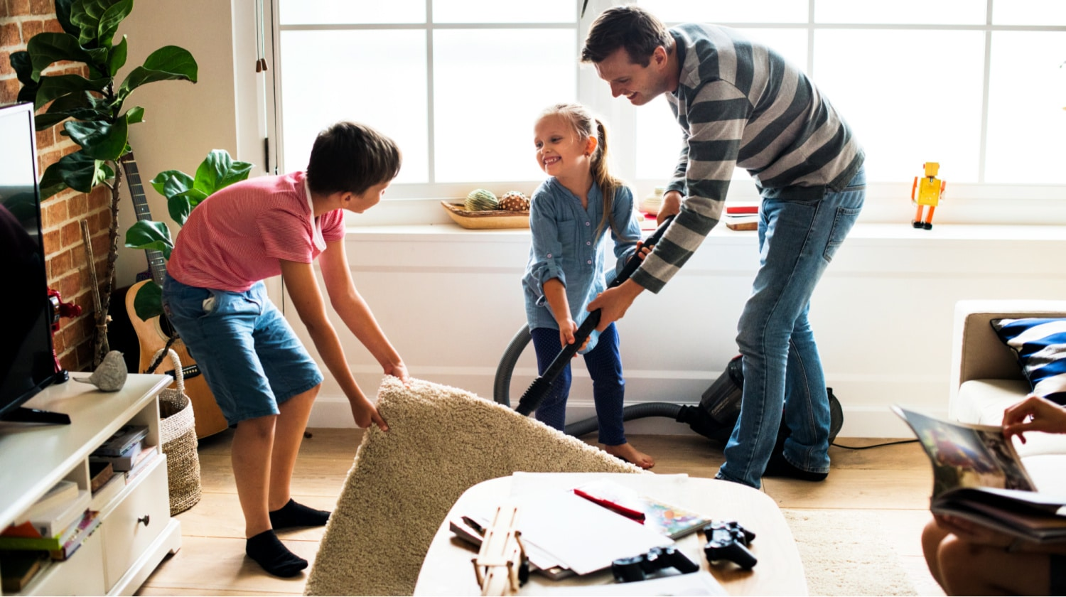 A man and two children vacuum under the living room rug