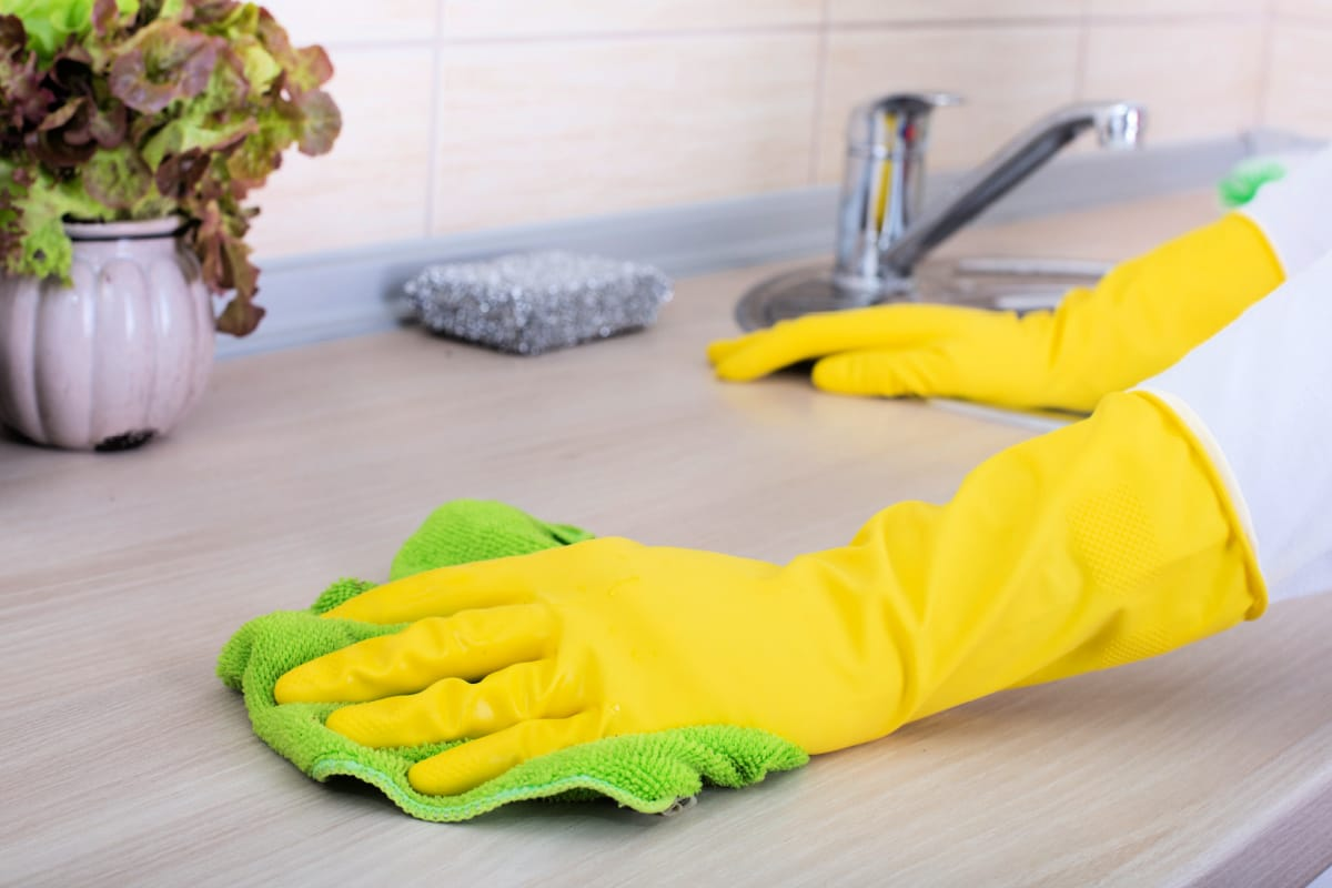 Person wearing rubber gloves to wipe counter and avoid dangerous passive combination of cleaning products