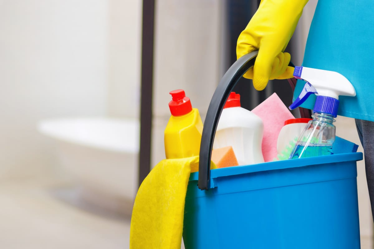 Person carrying bucket of cleaning supplies with bathroom in background