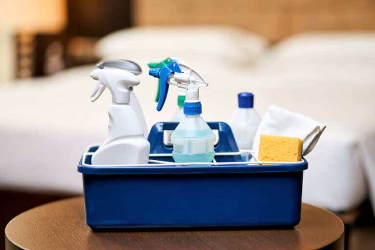 Bedroom Spring Cleaning supplies in a caddy on a table with a bed in the background