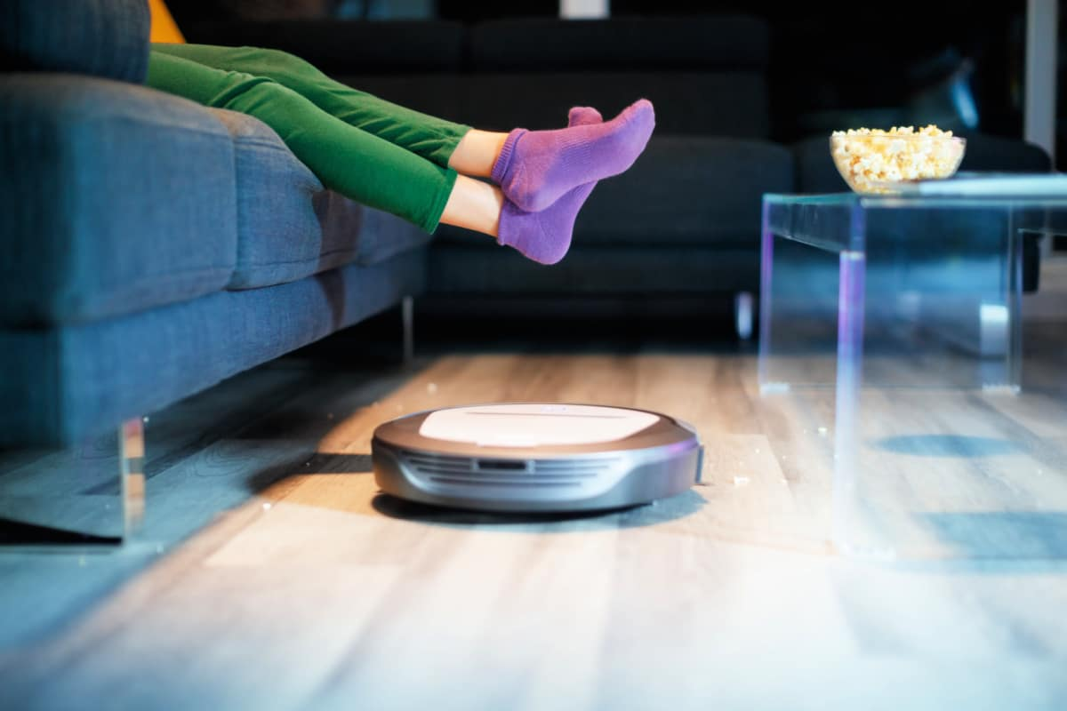 Female on sofa lifts legs as one of the best cleaning robots vacuums popcorn off the floor