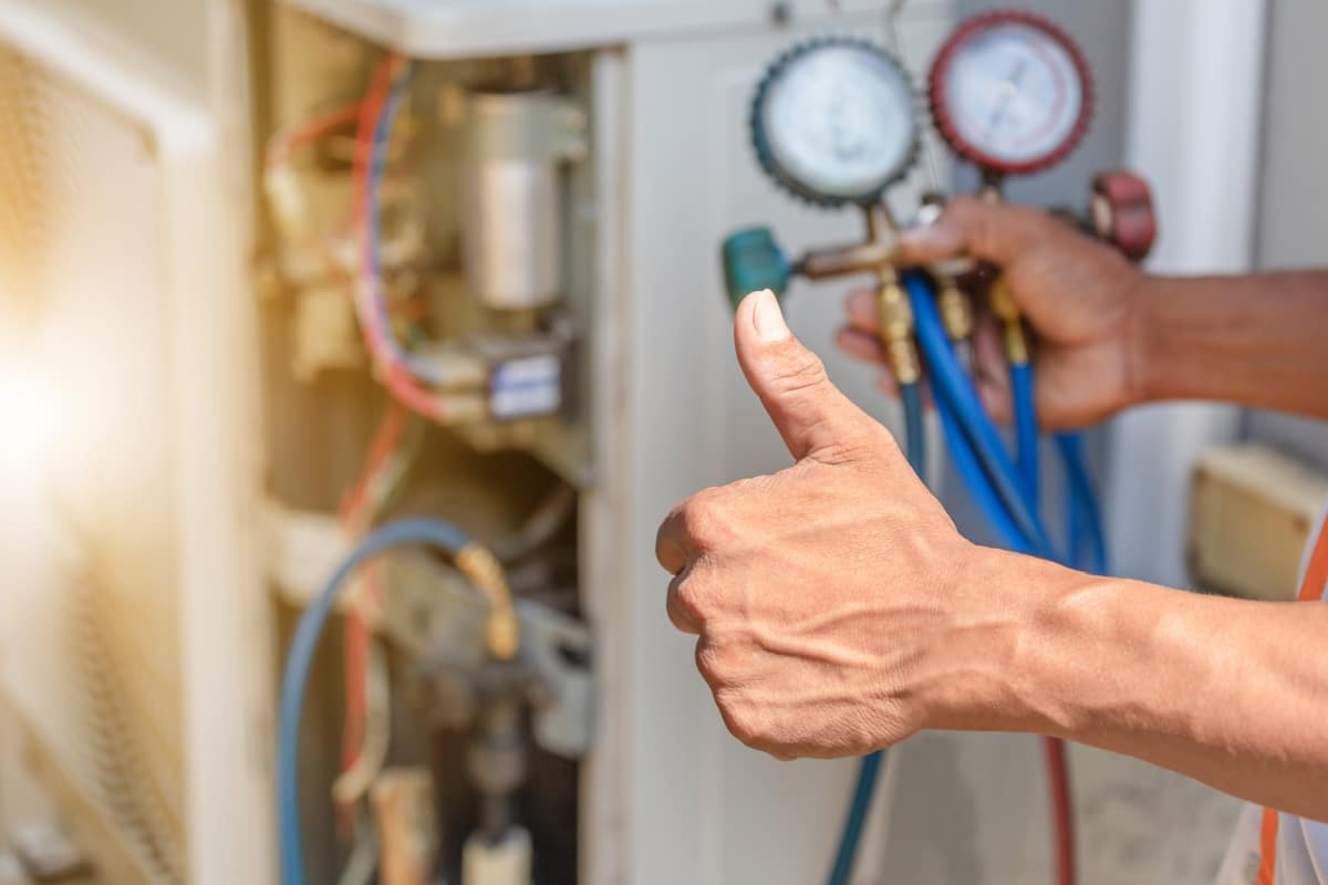 Male hand gives a thumbs up in front of an open furnace cover with pressure dials
