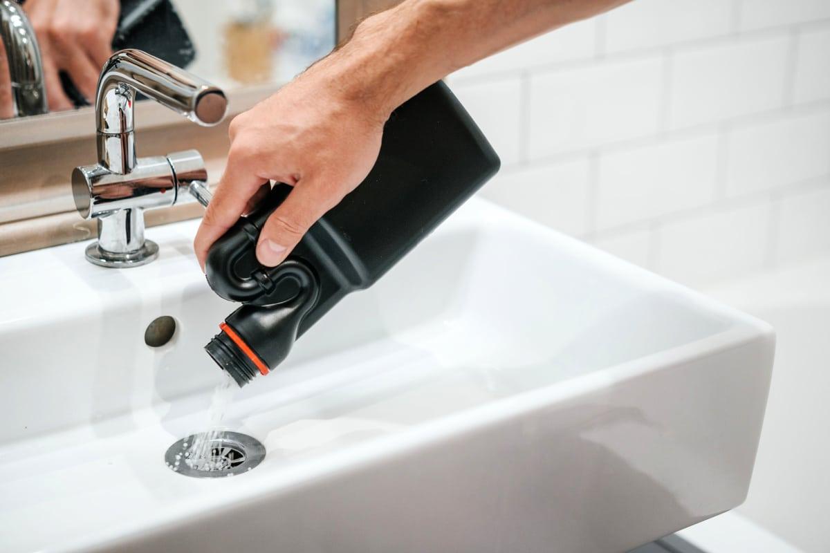 Male hand pours drain cleaner down bathroom drain