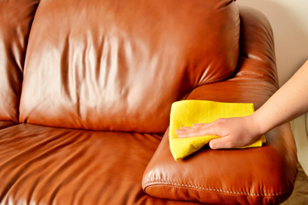 Female hand uses microfiber cloth to clean dust on leather sofa