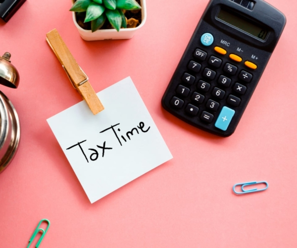 "Office supplies on a desk with ""Tax Time"" written on notepad"