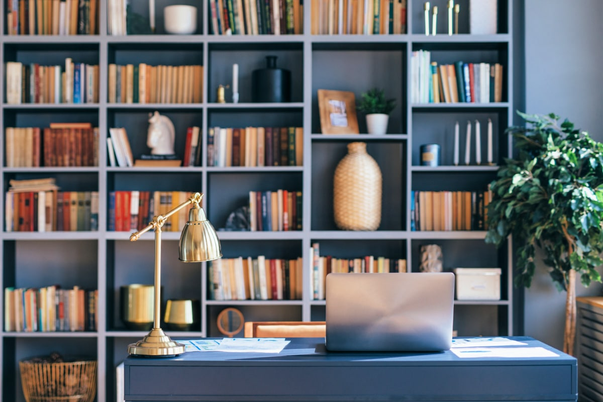 Decorative objects and books arranged on clean bookshelves behind desk in modern home office