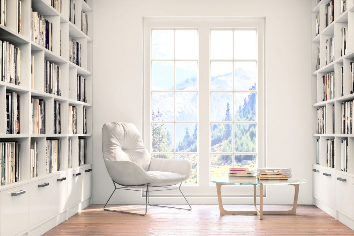 White leather reading chair in clean home library featuring floor to ceiling bookshelves