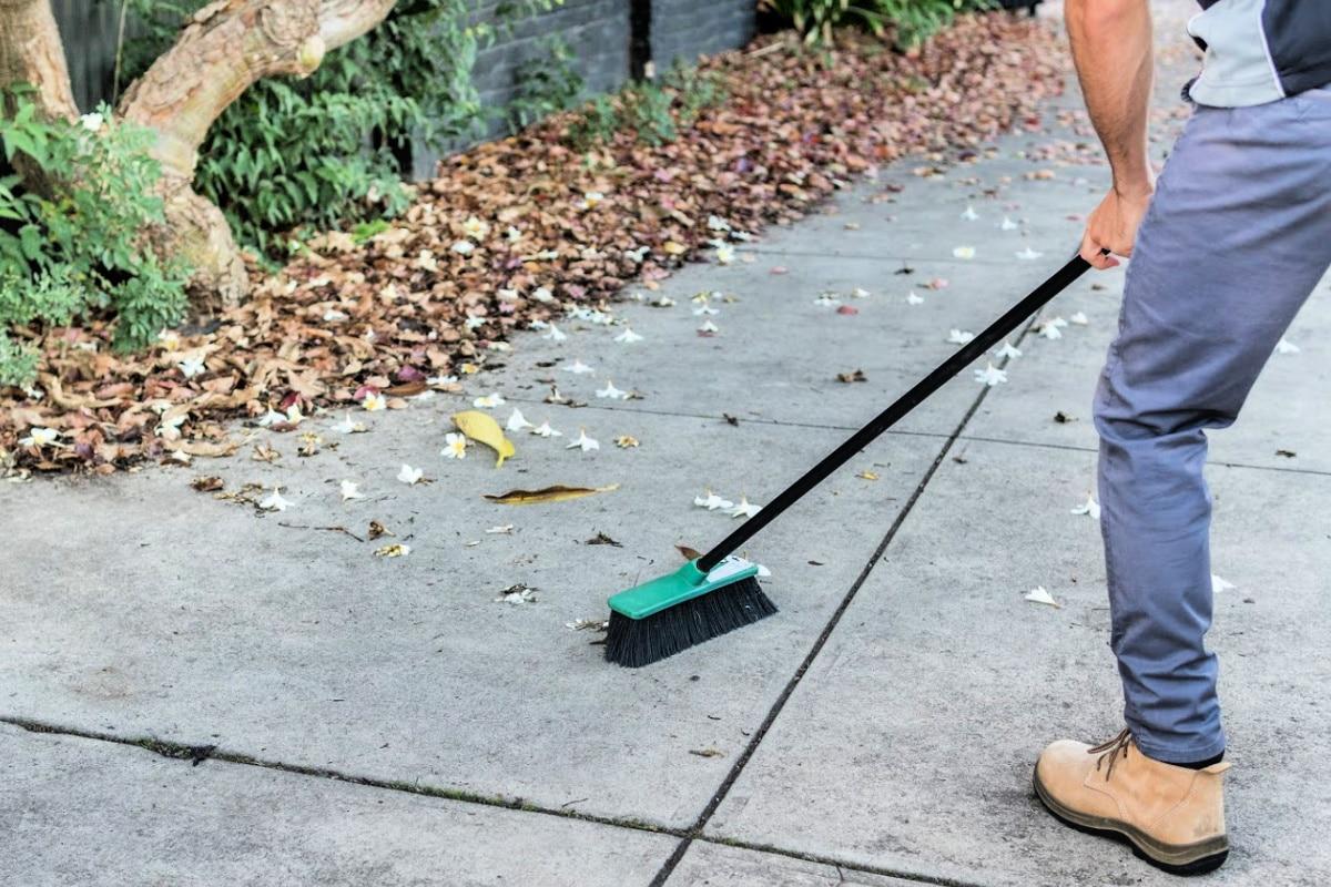 Man using push broom to clean dirty cement sidewalk