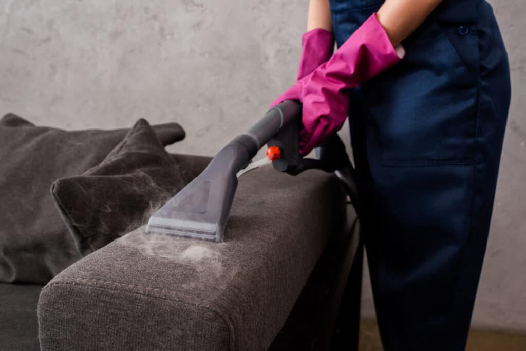 Woman demonstrates how to clean furniture with a vacuum