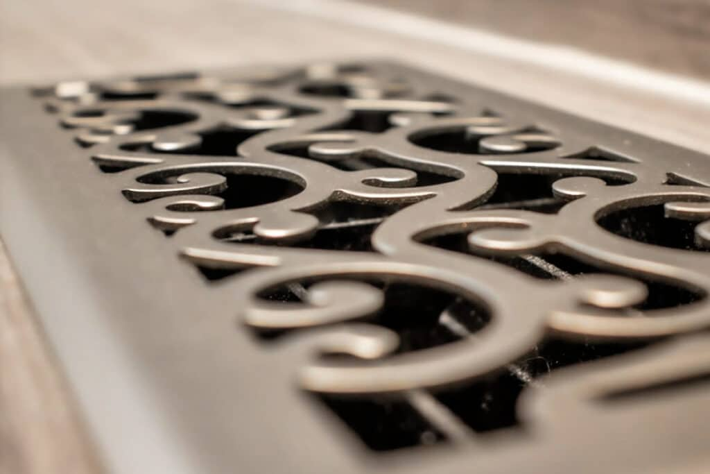 A decorative bathroom stainless steel metal silver floor vent with swirls