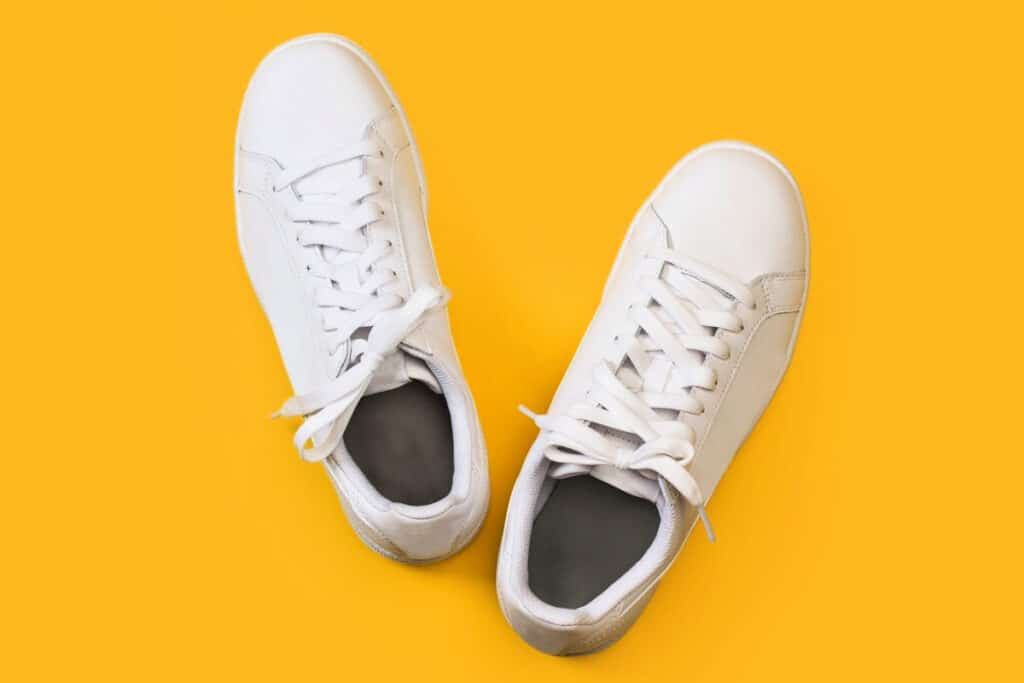 Top view of a pair of white sneakers on a yellow background
