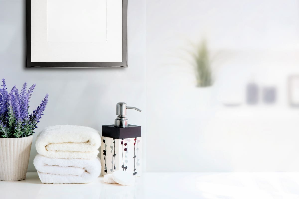 Toiletries and towels on a decluttered bathroom vanity