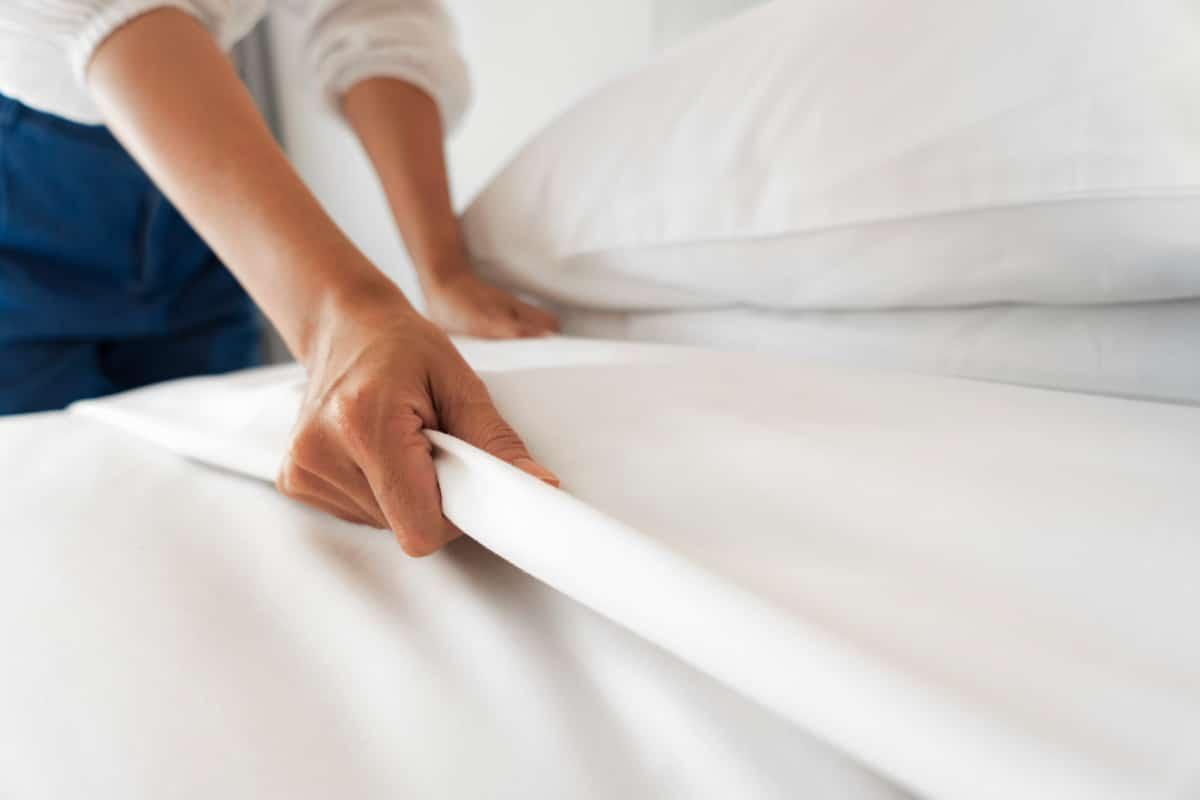 Female hands making bed in decluttered bedroom