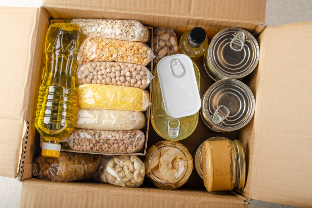 Food items in an open cardboard box for donation after pantry cleaning